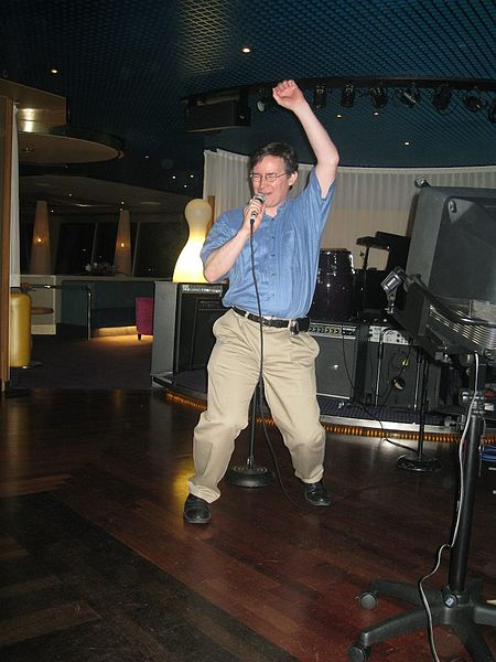 By Randal Schwartz (Flickr: John Rennie hits the karaoke mike) [CC BY-SA 2.0 (http://creativecommons.org/licenses/by-sa/2.0)], via Wikimedia Commons
